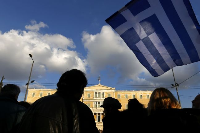 "People are silhouetted as a Greek national flag flutters during an anti-austerity pro-government demonstration in front of the parliament in Athens February 15, 2015. Greece has agreed with its European partners that there needs to be a ""national reform plan"" to deal with decades-long issues of the economy, its government spokesman said on Sunday. Greece and its euro zone partners are in difficult negotiations over demands by the new government of leftist Prime Minister Alexis Tsipras for an end to austerity and a renegotiation of Greece's debt. REUTERS/Yannis Behrakis  (GREECE - Tags: POLITICS BUSINESS CIVIL UNREST)"