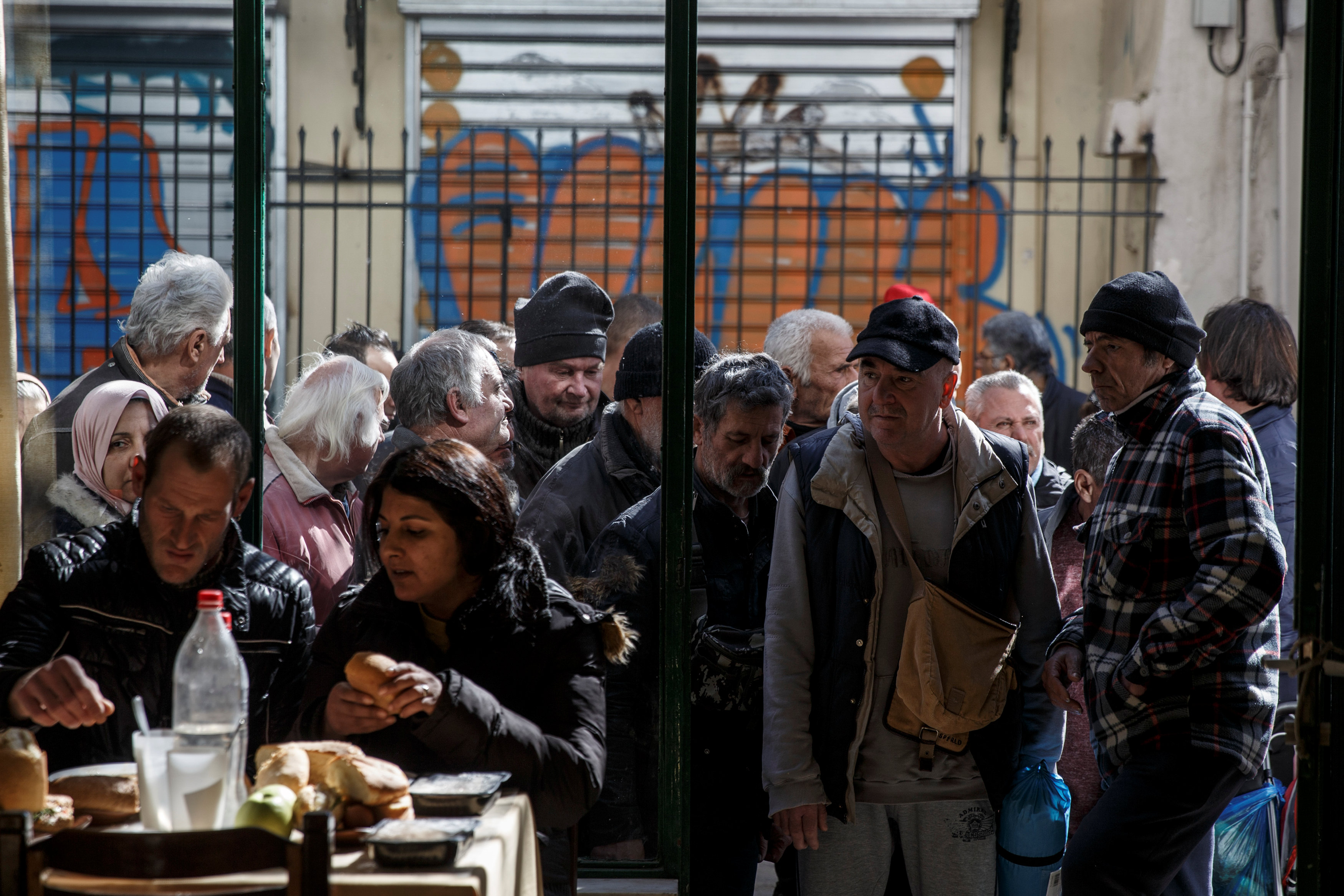 """People line up as they wait to enter a soup kitchen run by the Orthodox church in Athens, Greece, February 15, 2017. REUTERS/Alkis Konstantinidis            SEARCH """"POVERTY GREECE"""" FOR THIS STORY. SEARCH """"WIDER IMAGE"""" FOR ALL STORIES."""